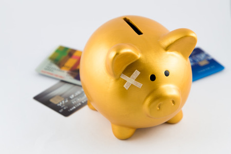 Piggy bank with plaster cross on his head. Behind is credit cards. They are in isolated white background.