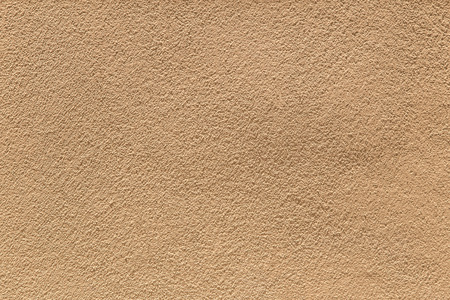knobby: Rough cement wall in brown color during the sunny day