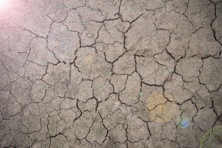 whether: Dark soil becomes drought and crack from hot whether. There is a light shine from the corner. Stock Photo