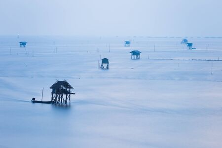 house float on water: Mist cover sea and floating house during rainy morning