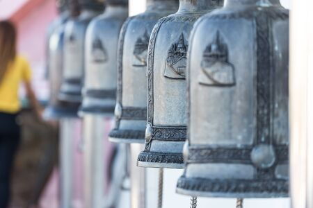 sonorous: Close up onto big bells hang on the bar in public temple of Thailand Stock Photo