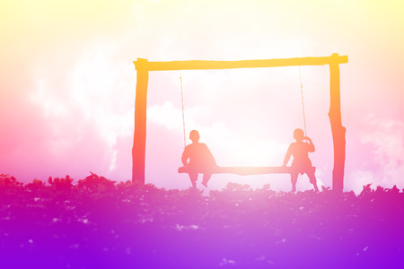 Silhouetted colorful scene of children sitting on swing bench of garden field