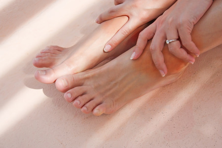 broken foot: Woman holding on her ankles due to getting pain from sport Stock Photo