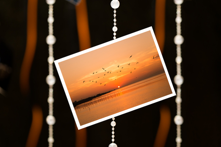 adhere: Sunrise picture adhere on blurred backdrop by string bead and ribbon Stock Photo