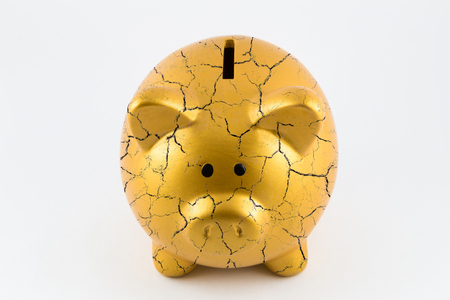 Front side of gold piggy bank cracked on isolated white background Banco de Imagens