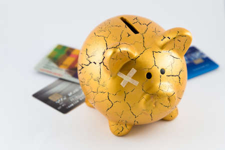 bonanza: Right side of gold piggy bank cracked with plaster and blurred credit cards on isolated white background