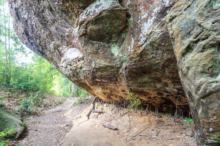 believing: Big rock on way inside Phukradueng national park in Loei province of Thailand. People put small stick to support below believing that the stick may maintain this rock for a long time.