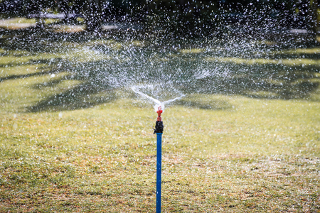 surround: Water splashing surround from the head of automatic sprinkle watering pipe on the grass field. Stock Photo