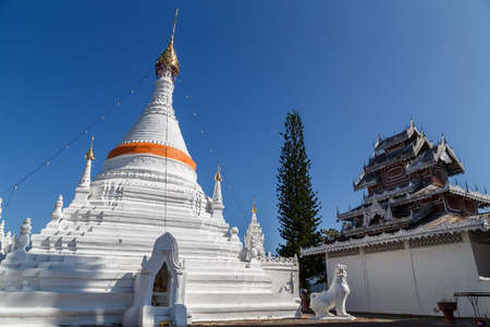 pra: White stupa and clear blue sky inside Wat Pra that doi kong mu, public temple in Maehongson, Thailand. The Buddha statue inside the box with Thai and English name describe its action. Stock Photo