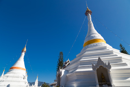 describe: Two stupa and clear blue sky inside Wat Pra that doi kong mu, public temple in Maehongson, Thailand. The Buddha statue inside the box with Thai and English name describe its action.