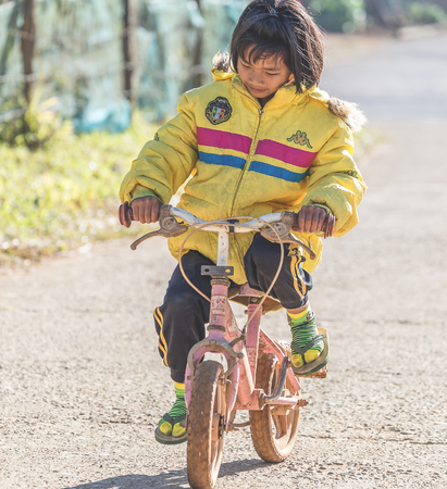 5 december: Maehongson, Thailand - December 10, 2016: Girl cycling her pink small bicycle in countryside schools parade for celebrating King of Thailands birthday of 5 December 2015.