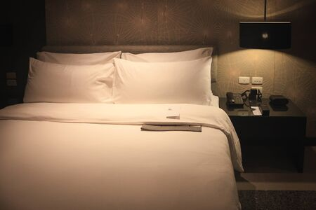 king size: King size bed, blanket and pillow with white cotton cover which shining by lamp on the wall.
