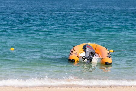 inflate boat: Inflated plastic speed boat floating on the shallow beach Stock Photo