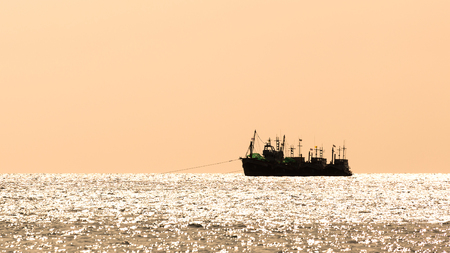 Silhouetted group of fishery boats which floating on waving water with background of sunset sky