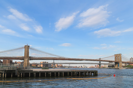 slightly: Wide angle view from riverside of Brooklyn bridge on blue sky with slightly cloud.