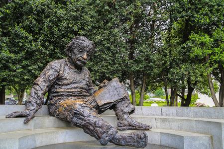 워싱턴 DC, 미국 -2014 5 월 16 일 : 배경으로 나무와 플랫 계단에 앉아 책을 읽고 알 버트 아인 슈타인의 철 동상
