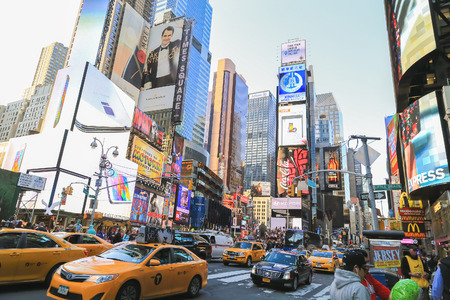 New York, USA - May 20, 2014: Crowd and traffic in time square area. Many yellow cabs on the road. Tall buildings and billboards are around this place. Editorial