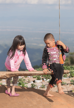Chiangmai, Thailand - December 7, 2015: Countryside boy and girl in pink shirt playing wooden swing hanging bench outdoor having agriculture area on mountain as background.