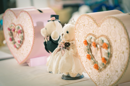 wedding night: Close focus on bride bear doll beside with groom bear doll and pink paper boxes in heart shape which decorated for wedding night. Stock Photo
