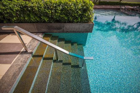 bajando escaleras: Seven stepping down stairs with stainless steel bar into water of mosaic swimming pool which reflected by trees shadow on surface and decorated by bush. Foto de archivo