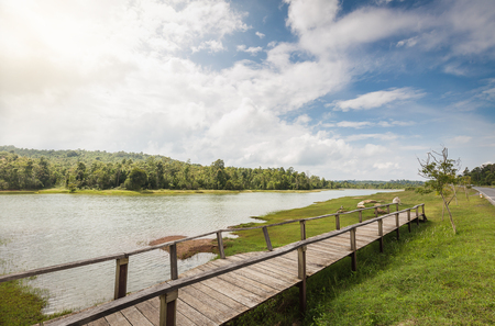 flood area: Wooden bridge across flood area of big lake which connect to green grass land which having forest with sunny blue sky as background in Thailand.