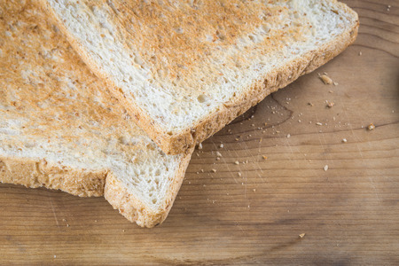 wheat toast: Close focus on edge of brown whole wheat toast on wood background with small crumb. Stock Photo