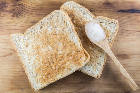 whole wheat toast: Top view on two brown whole wheat toast with sweet white jam on wooden teaspoon putting on wood background.