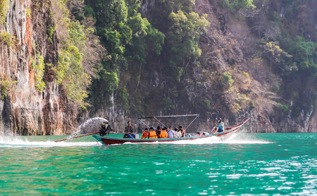 Suratthani, Thailand - April 14, 2015 : Travelling tourists travel by long trail boat with speed on green water surface for sight seeing nature in Thailands dam.