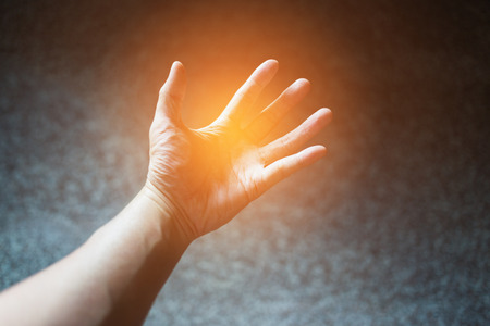 unfold: Abstract scene of powerful hand by soft orange light spreading on paw and fingers with blurry dark background. Stock Photo