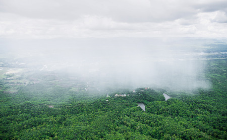 humid: Scenery of rain showing on green area covered by bush and tree of countryside in Thailand.