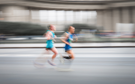 Blurry scene of unknown running men competed on road in fast motion. Banco de Imagens - 87407931