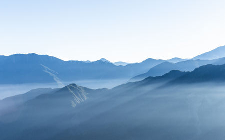 Hazy blue mountains of Zhushan inside Alishan Recreation Area in Taiwan covered by fog during sunrise in morning with bright winter sky.