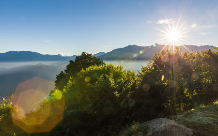 Morning view of Zhushan blue mountains range covered by haze with green forest and shining sunlight, forest area in Alishan, Taiwan.