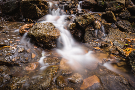 Waterfall with smooth cool water flowing through rocks and stones of rainy season in tropical forest of Thailand. Stock Photo