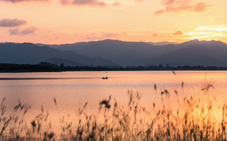 Sunset scene of rural lake surround by forest and mountain ranges. Fishing boat floating on water surface to find fishes.