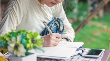 Young woman drawing and writing on white notebook on table outdoor in garden.