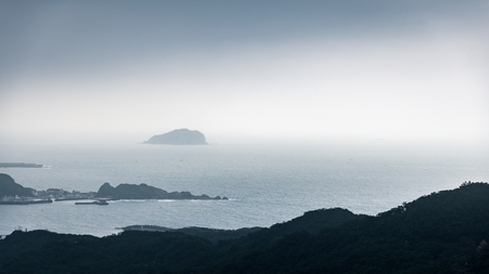 Aerial view from dark mountain to misty sea of Jiufen, Taiwan after raining.