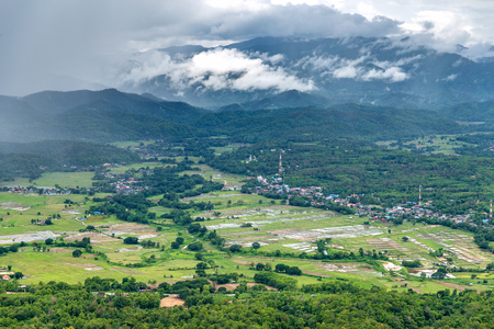 Panoramic view on green tropical forest on foothill of hazy mountain range of Lampang, Thailand.