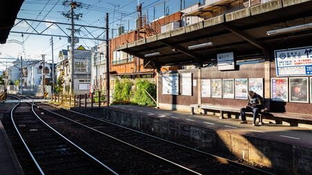 Kyoto, Japan - November 20, 2018: Tourist sit on bench waiting train of Keifuku Electric Railroad Kitano Line at Ryoanji station.
