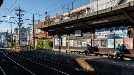 Kyoto, Japan - November 20, 2018: Tourists sit on bench waiting train of Keifuku Electric Railroad Kitano Line at Ryoanji station. Editorial