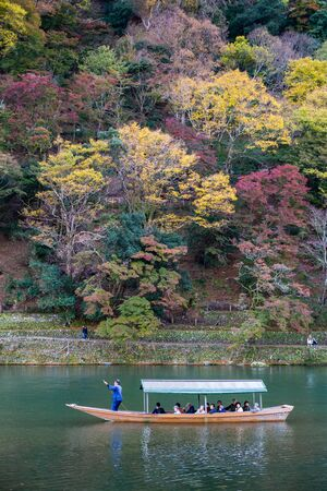 Kyoto, Japan - November 20, 2018: Rowing boat with tourists on Hozugawa river at Arashiyamas colorful trees on moutain during autumn. Editorial