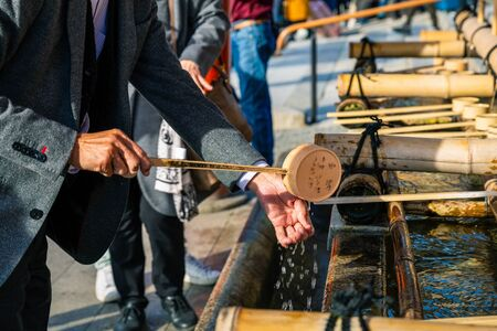 Kyoto, Japan - November 21, 2018: Tourist pouring holy water by water dipper on hand to wash before entering to temple. Editorial
