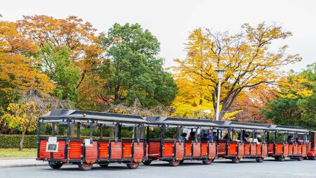 Osaka, Japan - November 26, 2018: Red car waiting tourist for sight seeing osaka castle with background of colorful trees during autumn season.