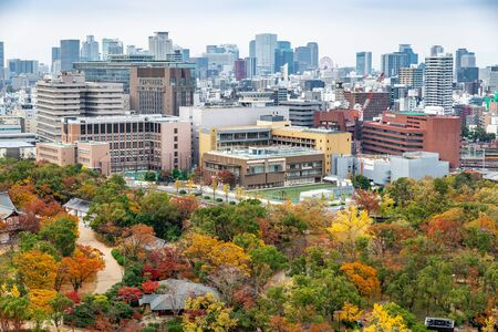 Osaka, Japan - November 26, 2018: Aerial view of Osaka city from top of Osaka castle, park covered by colorful trees during autumn season. Editorial