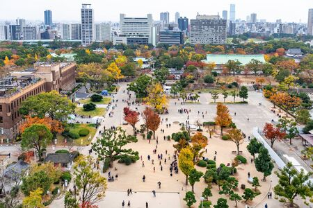 Osaka, Japan - November 26, 2018: Aerial view of Osaka city from top of Osaka castle, park with crowd covered by colorful trees during autumn season. Editorial