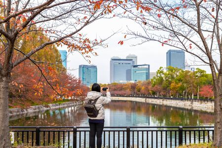 Osaka, Japan - November 26, 2018: Young woman taking photo of city reflecting pond surrounded by changing color of tree in autumn. Editorial
