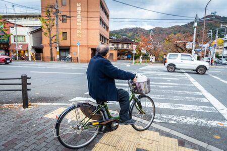Kyoto, Japan - November 19, 2018: Japanese man in black cloth stop bike and wait to cross a crosswalk at traffic junction in Kyoto.