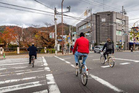 Kyoto, Japan - November 19, 2018: People riding bikes crossing a crosswalk on road junction in city of Kyoto. Editorial