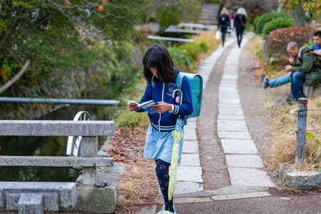 Kyoto, Japan - November 19, 2018: Japanese girl concentrated on book while walking on local walkway.