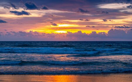 Colorful cloudy sky with sunlight reflecting on andaman sea of Phuket beach, Thailand at sunset.